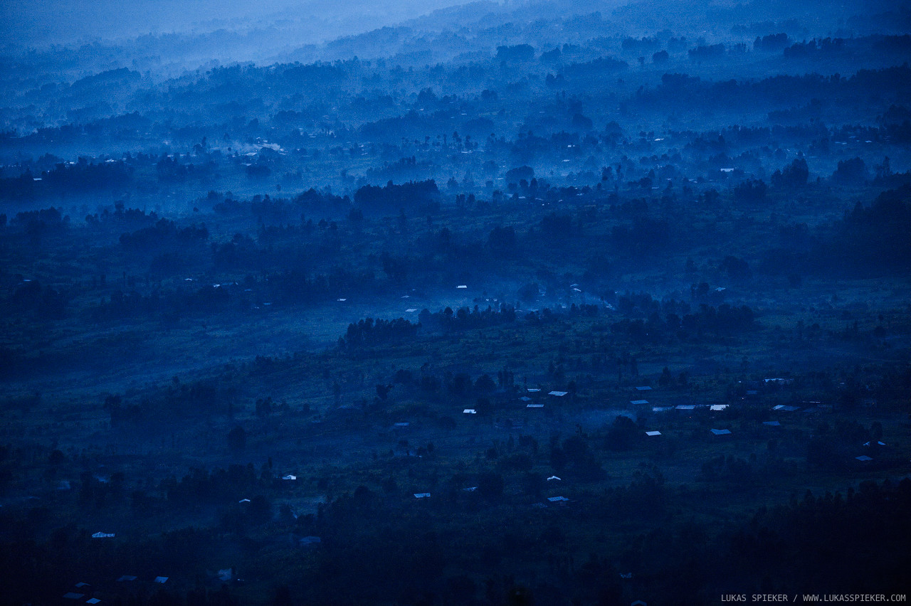 Night falls in the hills at the foot of Mount Muhabura of the Virunga volcanoes on the border between Rwanda, Congo, and Uganda on April 7, 2014. Mist mixes with smoke of burned eucalyptus wood. The beauty of Rwanda's hills contrasts with the horror that happened here twenty years ago during the 1994 genocide.