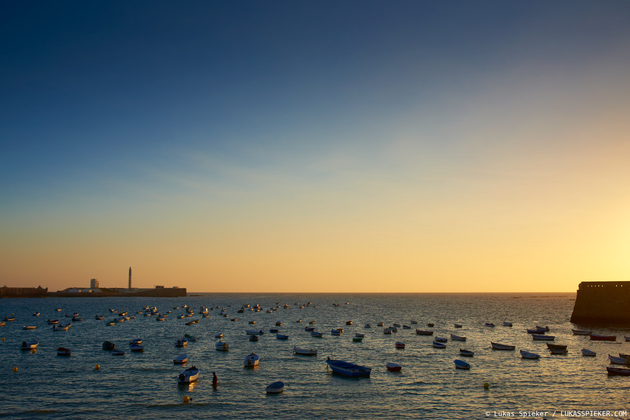 Fisherboats lie at the beach La Caleta in Cadiz. The fort San Sebastian (left) and the Santa Catalina castle (right) were built in 1598 to deter further British attacks in the Anglo-Spanish War (1585–1604).