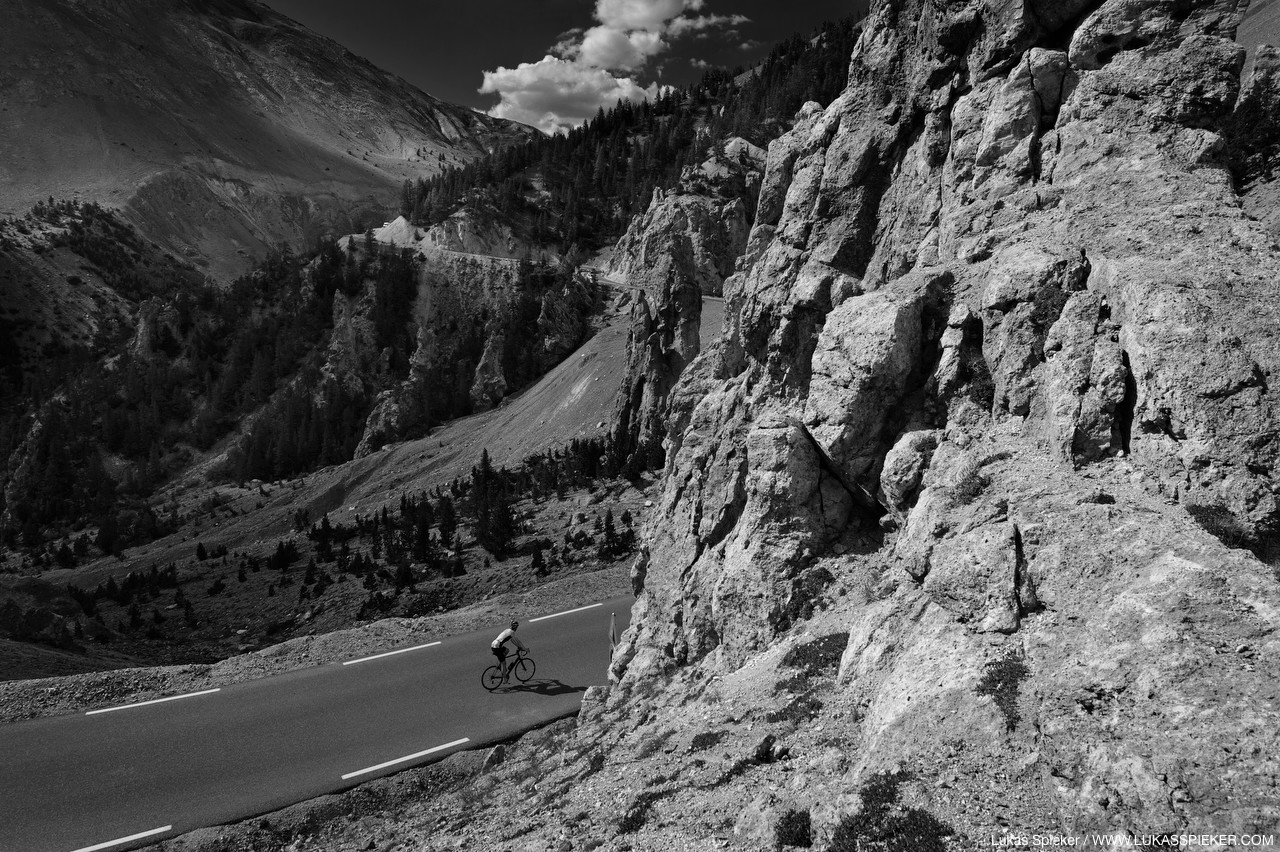 A cyclist climbs the road to Col d'Izoard (2360 m) in the French alps leading through dramatic rock formations and pinnacles – La Casse Deserte.