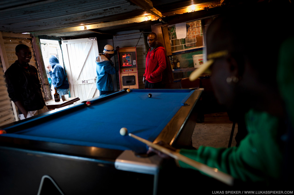 Men play billard in a bar in Imizano Yethu, Hout Bay, South Africa. Imizano Yethu is such an informal settlement, situated in Hout Bay, South Africa. In Imizamo Yethu, 20'000 to 30'000 people live in a 18 hectare area with little or no infrastructure, two-thirds of them in informal dwellings and shacks. Many of the shacks do not have electricity. Only 19 percent of people have access to piped water in dwelling. Rain often moistens the shack interiors as the roofs are leaky. Landslides threaten the top shacks on the hill when winter brings heavy rainfalls. Unemployment rate is between 40 to 60 percent, and alcohol and substance abuse are major problems. HIV and tuberculosis prevalence is high.