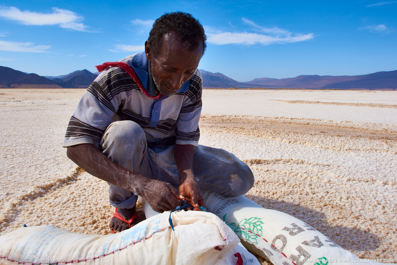 Aras and his family harvest the salt at the shore of Lac Assal in Djibouti. Salt extraction from Lac Assal by local tribes enabled trading with caravans from the highlands of Abyssinia. The bartering for coffee, sorghum, ivory, and slaves was a source of wealth for the local Afar tribes.