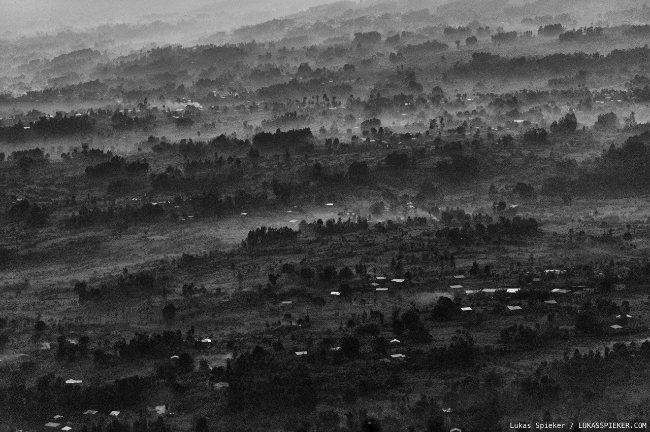 Night falls in the hills at the foot of Mount Muhabura of the Virunga volcanoes on the border between Rwanda, Congo, and Uganda. Mist mixes with smoke of burned eucalyptus wood.