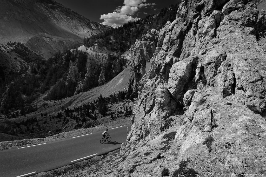 A cyclist climbs the road to Col d'Izoard (2360 m) leading through dramatic rock formations and pinnacles – La Casse Deserte.