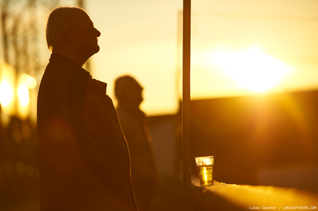 The sun sets as fans watch Saturday's lower league football match.